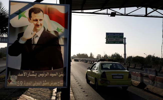 A poster of Syrian President Bashar al-Assad is seen on the main road to the airport in Damascus