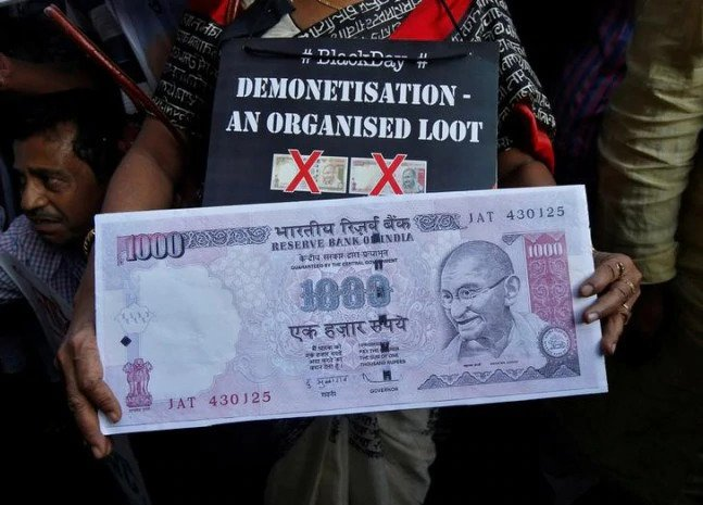 A demonstrator holding a replica of the old 1,000 rupee note during a protest organised by the Congress party, to mark a year since demonetisation was implemented by Prime Minister Narendra Modi, in Kolkata on November 8, 2017.