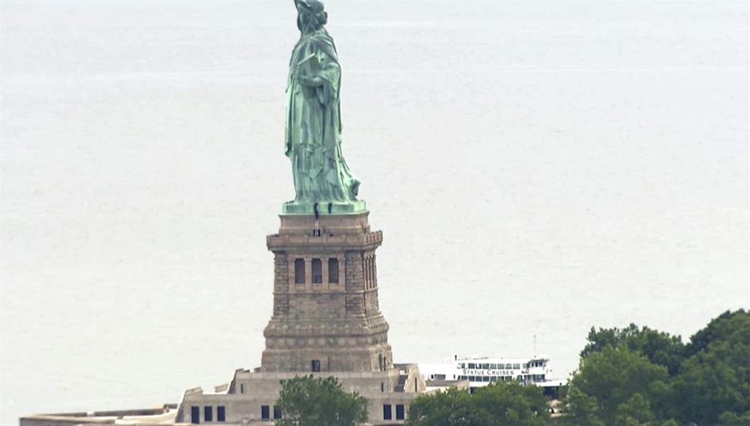 People climb on the pedestal of the Statue of Liberty in New York Harbor.