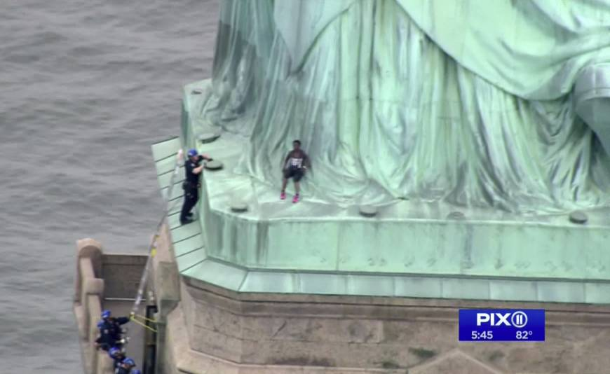 A person leans against the robes of the Statue of Liberty on Liberty Island, as one of the police officers climbed up on a ladder to stand on a ledge nearby talking the climber into descending in New York.