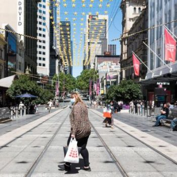 Shoppers wearing masks cross Bourke Street Mall in central Melbourne on Boxing Day 2020