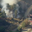 Los Angeles firefighters battle brush fire along Sepulveda Pass