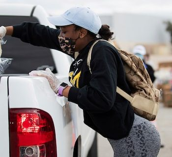 Volunteer Taiya Edwards, 18, places a pack of tortillas on a vehicle during the Neighborhood Super Site food distribution event organized by the Houston Food Bank and HISD, Sunday, Feb. 21, 2021, in Houston. (Marie D. De Jesús/Houston Chronicle via AP)