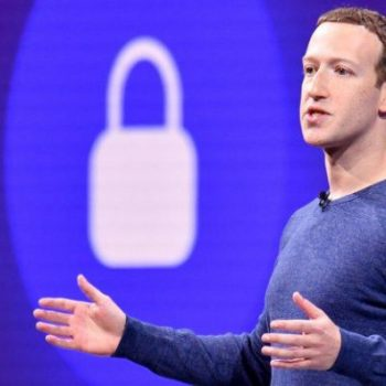 Mark Zuckerberg gestures with arms open in front of a padlock symbol on stage during a privacy speech