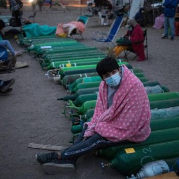 A man sits on top of empty oxygen cylinders, waiting for a shop to open to refill his tank, in the Villa El Salvador neighborhood, as the lack of medical oxygen to treat COVID-19 patients continues in Lima, Peru, Tuesday, April 6, 2021.