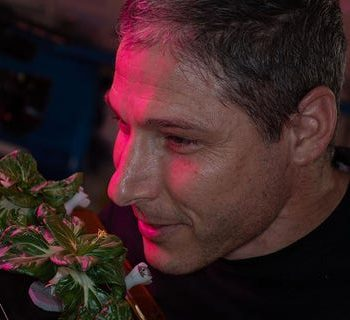 NASA astronaut and Expedition 64 flight engineer Michael Hopkins smells 'Extra Dwarf' pak choi plants growing aboard the International Space Station on March 26, 2021. The plants were grown for the Veggie study, which is exploring space agriculture as a way to sustain astronauts on future missions to the Moon or Mars.