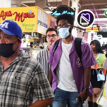 Masked and unmasked people make their way through Grand Central Market in Los Angeles, California on June 29, 2021 as World Health Organization (WHO) urges fully vaccinated people to continue wearing masks with the rapid spread of the Delta variant. (FREDERIC J. BROWN/AFP via Getty Images)